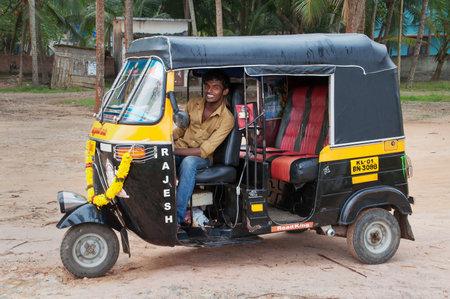 village man: KOVALAM, INDIA - DEC 28, 2014: Indian auto rickshaw with taxi driver man in fishing village. Kovalam. Kerala. India