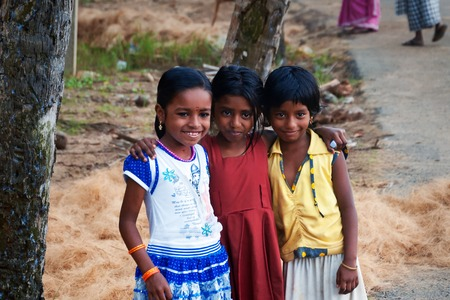 kovalam: KOVALAM, INDIA - DEC 28, 2014: Unidentified three Indian girls on the street in fishing village. Kovalam. Kerala. India