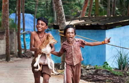 kovalam: KOVALAM, INDIA - DEC 28, 2014: Unidentified two Indian boys with dog on the street in fishing village. Kovalam. Kerala. India