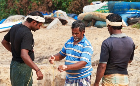 varkala: VARKALA, INDIA - DEC 30, 2014: Unidentified Indian Fishermen with fishing net on beach in Varkala. Kerala. India