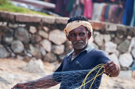 pecheur: VARKALA, INDE - 30 décembre 2014: Pêcheur indien non identifié avec un filet de pêche sur la plage à Varkala. Kerala. Inde