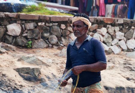 pescador: VARKALA, INDIA - 30 de diciembre 2014: Pescador indio no identificado con red de pesca en la playa en Varkala. Kerala. India