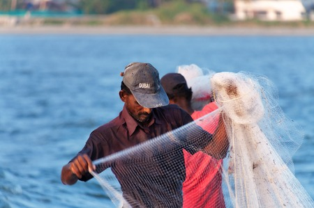 india fisherman: Fort Kochi, India - Jan 6, 2015: Unidentified Indian Fisherman with net on the beach of Fort Kochi. Kerala