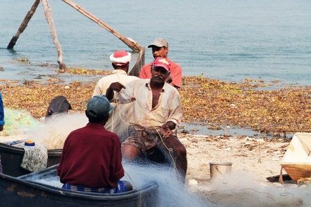 kochi: Fort Kochi, India - Jan 6, 2015: Unidentified Indian Fishermen on boat with net on the beach of Fort Kochi. Kerala