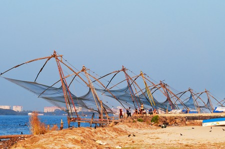 chinese fishing nets: Fort Kochi, India - Jan 6, 2015: Tourists wait for sunset near Chinese Fishing nets in Fort Kochi. Kerala. India