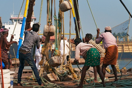 pull out: Fort Kochi, India - Jan 6, 2015: Unidentified Indian fishermen pull out their Chinese fishing net from sea in the beach of Fort Kochi. Kerala Editorial