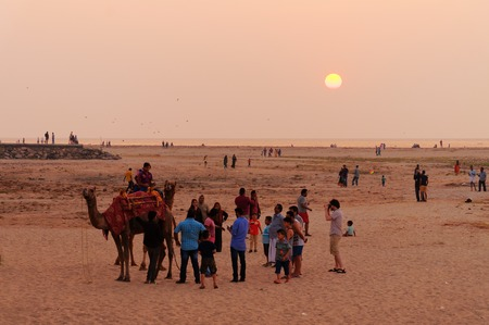 indian ocean: Fort Kochi, India - Jan 6, 2015: Indian local tourists with a camel on the beach at sunset