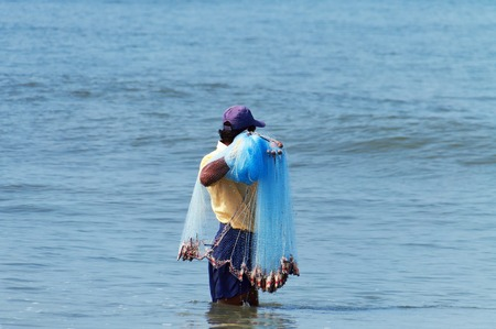 kochi: Fort Kochi, India - Jan 7, 2015: Unidentified Indian fisherman catch fish by throwing net. Fort Kochi is a region in the city of Kochi in the state of Kerala, India. Editorial