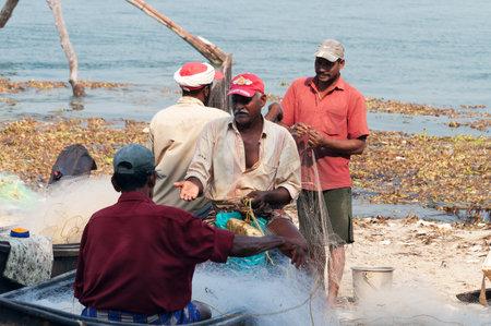 chinese fishing nets: Fort Kochi, India - Jan 6, 2015: Unidentified Indian Fishermen on boat with net on the beach of Fort Kochi. Kerala