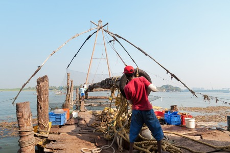chinese fishing nets: Fort Kochi, India - Jan 6, 2015: Unidentified Indian fishermen descend their Chinese fishing net into the sea  in the beach of Fort Kochi. Kerala