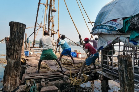 kochi: Fort Kochi, India - Jan 6, 2015: Unidentified Indian fishermen pull out their Chinese fishing net from sea in the beach of Fort Kochi. Kerala Editorial