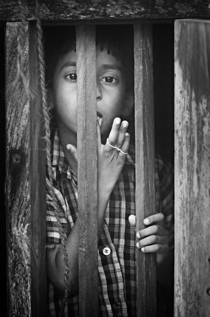 kovalam: Kovalam, India, Dec 28, 2014: Unidentified Indian boy looks through a window at home in small fishing village. Black and white Editorial