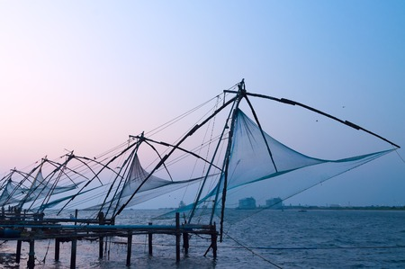 india fisherman: Chinese Fishing nets at sunset. Fort Kochi. Kerala. India Stock Photo