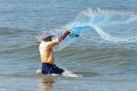 fish net: Fort Kochi, India - Jan 7, 2015: Unidentified Indian fisherman catch fish by throwing net. Fort Kochi is a region in the city of Kochi in the state of Kerala, India. Editorial