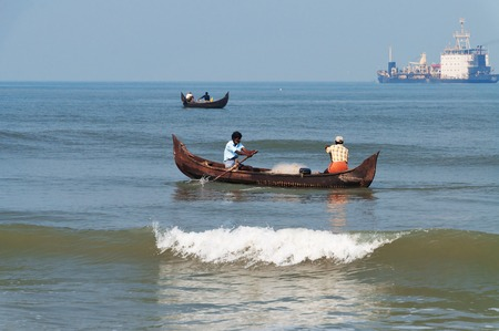 kochi: Fort Kochi, India - Jan 7, 2015: Unidentified Indian fishermen in a boat catch fish. Fort Kochi is a region in the city of Kochi in the state of Kerala, India.