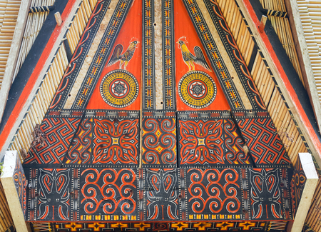 wood carvings: Rantepao, Indonesia - Dec 07, 2015: Toraja traditional house wood carvings and paitings with cock