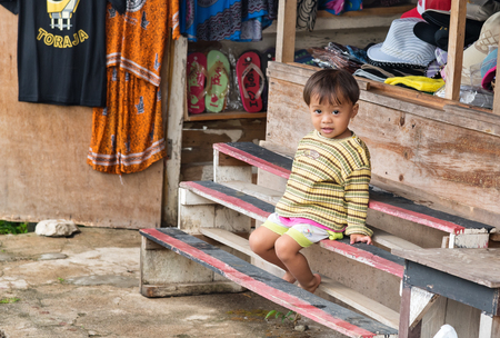 toraja: Rantepao, Indonesia - Dec 07, 2015: One unidentified child on bench at the shop in the village of Tana Toraja, Sulawesi