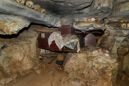 coffins: Skulls and coffins in cave. Londa is cliffs and cave old burial site in Tana Toraja. Galleries of tau-tau on balcony guard the graves. Inside theres a collection of coffins. South Sulawesi, Indonesia