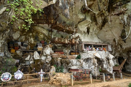 coffins: Tana Toraja, Indonesia - Dec 09, 2015: Londa is cliffs and cave old burial site in Tana Toraja. Galleries of tau-tau on balcony guard the graves. Inside theres a collection of coffins. South Sulawesi Editorial