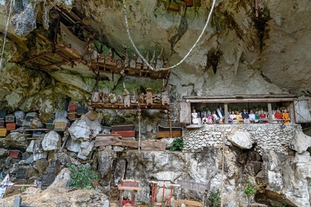 coffins: Tana Toraja, Indonesia - Dec 08, 2015: Londa is cliffs and cave old burial site in Tana Toraja. Galleries of tau-tau on balcony guard the graves. Inside theres a collection of coffins. South Sulawesi