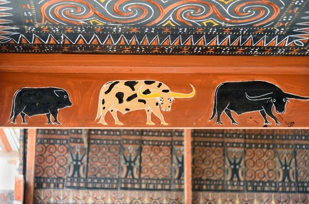 wood carvings: Rantepao, Indonesia - Dec 09, 2015: Toraja traditional house wood carvings and paitings with different buffaloes and pig
