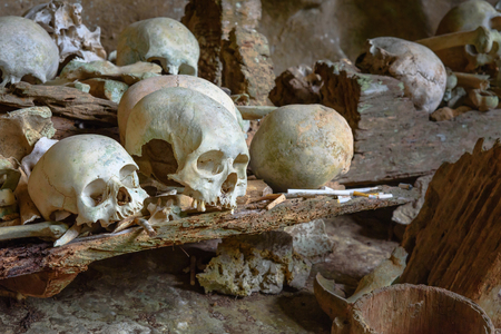 coffins: Pile of skulls by the entrance to Tampang Allo burial cave of the royal family. There are coffins are placed in caves or hanging from the cliff and wooden statues tau-tau guard the graves. Tana Toraja. South Sulawesi. Indonesia Stock Photo