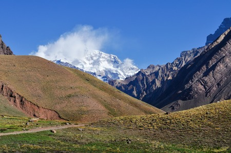 clambering: Aconcagua in the clouds. Aconcagua is the highest mountain in the Americas at 6960m. Province of Mendoza. Argentina Stock Photo