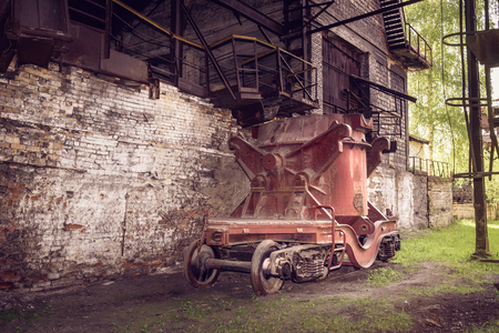 cast iron red: Old steel buckets to transport the molten iron, mounted on railway platforms in blast furnace workshop on Mining and metallurgical plant