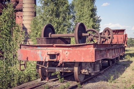 flatcar: Old flat wagon with railcar wheelset. Old industrial railway cars on on Mining and metallurgical plant