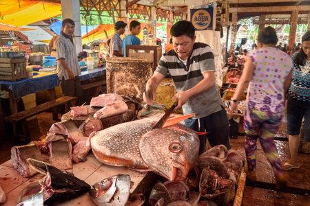 Tomohon, Indonesië - 23 december 2015: Indonesische mens snijdt de grote vis op Tomohon Traditional Market. North Sulawesi