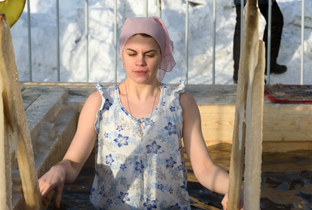 Nizhny Tagil, Russia - January 19, 2016: Woman bathes into cold water of ice-hole on Epiphany day. Traditional ice swimming in Orthodox church Holy Epiphany Day