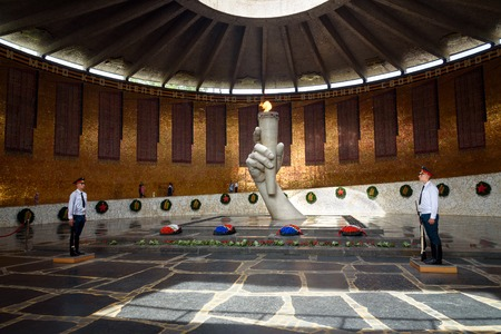 guarded: Volgograd, Russia - Aug 31, 2016: Hall of Military Glory. In centre of hall is sculpture of hand holding torch with Eternal Fire. Eternal Fire is guarded by soldiers. Memorial complex Mamayev Kurgan