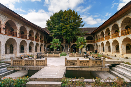 Sheki, Azerbaijan - September 13, 2016: View of the inner courtyard of Upper caravanserai is a historical monument in Sheki 18th-19th centuries. It was used by merchants to store their goods in cellars, who traded on the first floor, and lived on the seco
