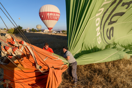 rock formation: Goreme, Turkey - October 16, 2016: Hot air balloon is deflated after landing in the morning. Cappadocia. Nevsehir Province