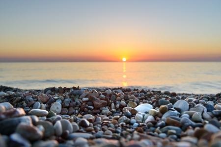 Sea beach sunrise in Cirali Olympos beach. Antalya Province. Turkey. Selective focus on stones