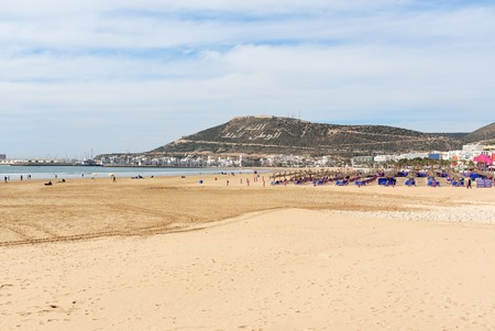 Long, wide beach in Agadir city, Morocco. The hill bears the inscription in Arabic: God, Country, King