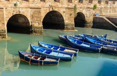 View of Old Fortress Sqala du Port and blue fishing boats in Essaouira. Morocco