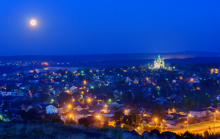 View of Nizhny Tagil town with Alexander Nevsky church at night with full moon. Russia