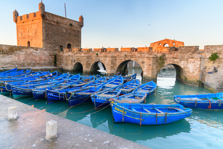 bastion: Essaouira, Morocco - January 01, 2017: View of Old Fortress Sqala du Port and blue fishing boats Editorial