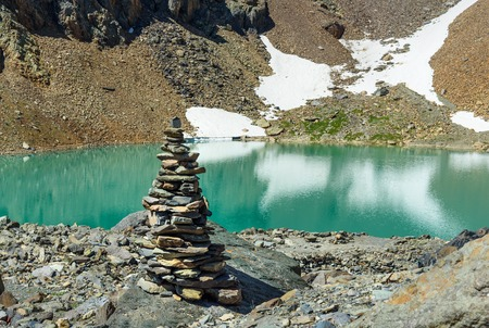 Stones pyramid at Blue Lake on mountain in Aktru valley. Lake located at an altitude of 2840 m. North-Chuiskiy Range. Altai Republic, Siberia. Russia Stock Photo