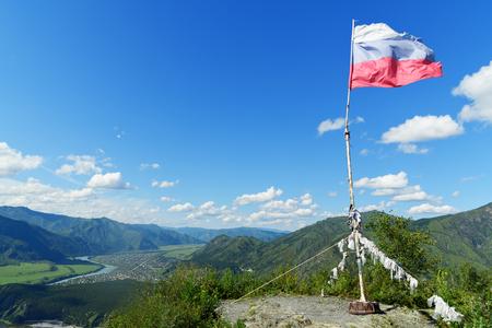 Russian flag on top of mountain Camel near Chemal. Altai Republic, Siberia. Russia