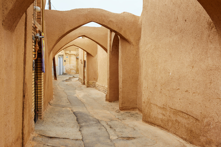 Narrow street with arches of old adobe Yazd city. Iran 版權商用圖片