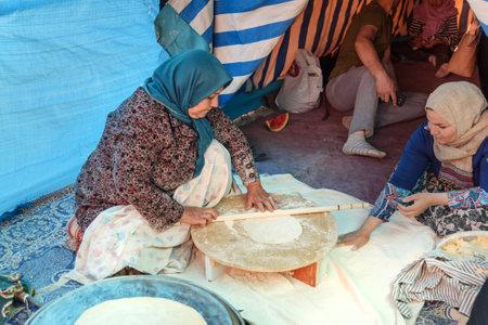 Shiraz, Iran - March 24, 2018: Iranian woman preparing traditional bread on the street market Editöryel