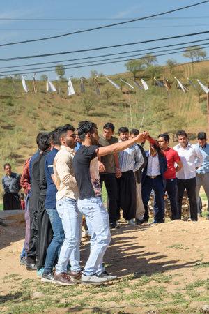 Lorestan Province, Iran - April 1, 2018: Iranian men dancing Lurish Cupi dances on wedding ceremony in the village.