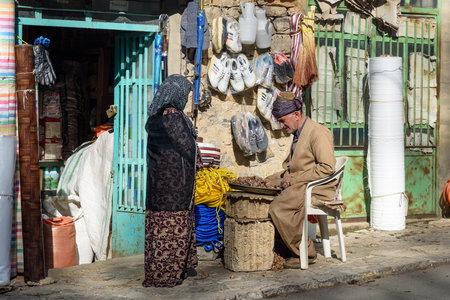 Howraman, Kurdistan Province, Iran - April 5, 2018: Kurdish man cleans and crack walnuts on the street near shop in Howraman village or Uraman Takht in Zagros Mountain Editöryel