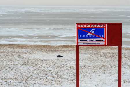 Sign with inscription in Russian Swimming is prohibited near Gulf of Finland in winter Stock Photo
