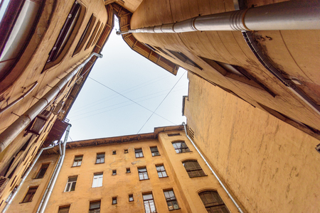 Courtyard-well. The bottom view upwards in snowfall in Saint Petersburg, Russia