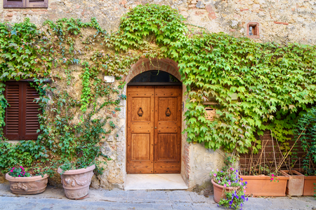 Old house decorated with flowers on sunny day in Monteriggioni, Tuscany, Italy Stock Photo