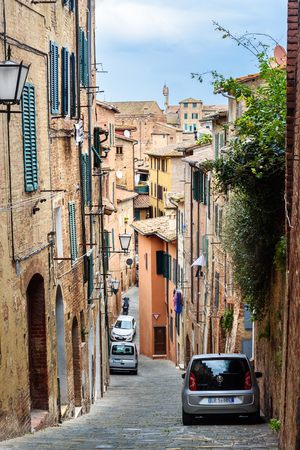 Siena, Italy - October 02, 2018: Medieval narrow street Via Lombarde in old city Siena 新聞圖片