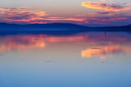 View sunrise in lagoon Orbetello on peninsula Argentario in Tuscany. Italy